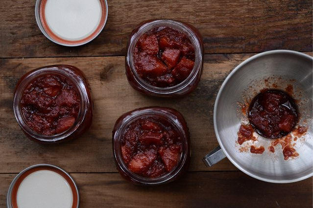 filling jars with quince preserves by Camille Storch