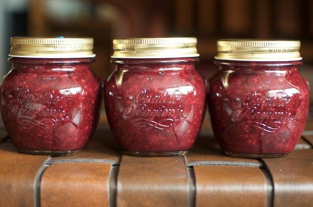 three jars of low sugar blackberry rhubarb jam on a bench