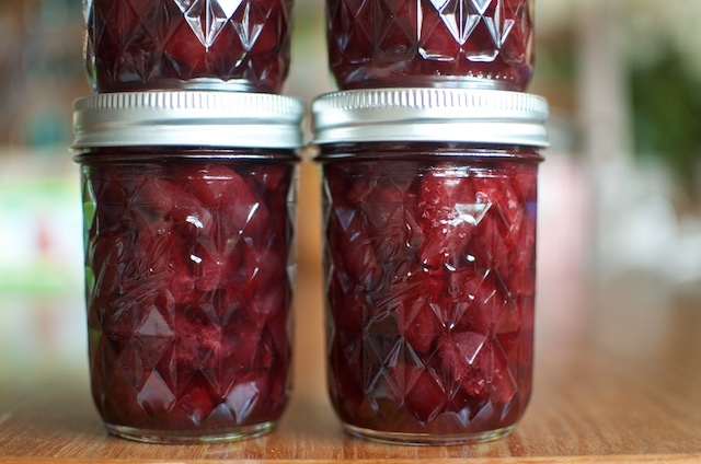 Lightly pickled sweet cherries in jars close-up