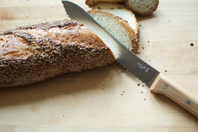 A seeded baguette, being sliced by an Opinel bread knife.