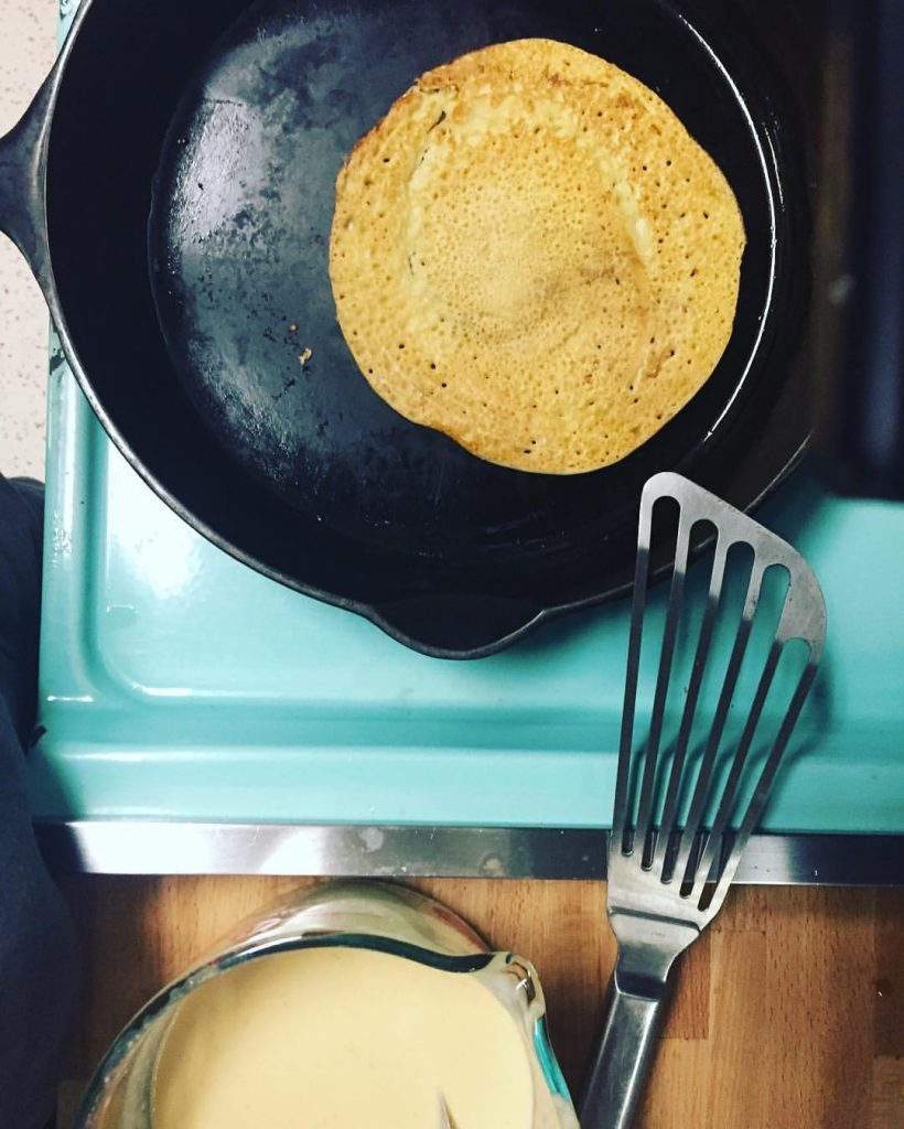 Cooking homemade chickpea flatbread in a cast iron skillet.