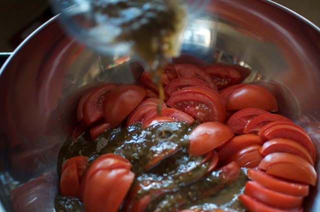 pouring dressing into marinated dehydrated tomatoes