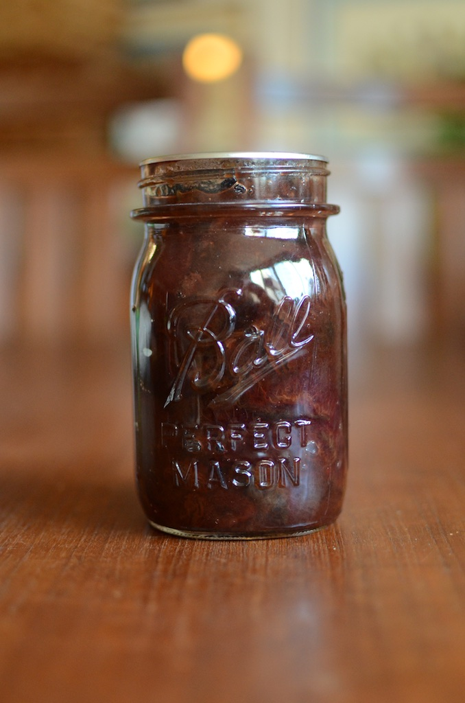 A jar of plum conserve with golden raisins and walnts