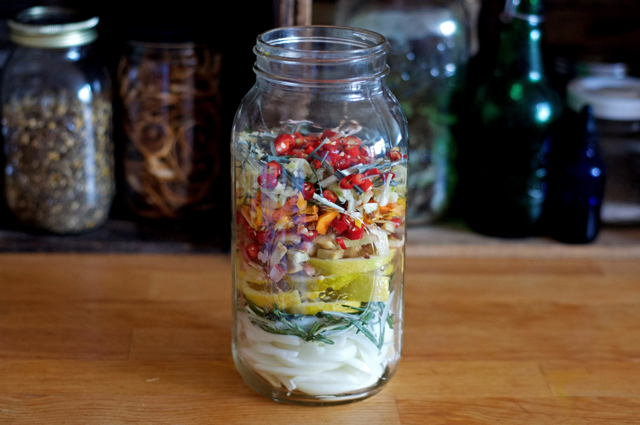 Ingredients layered in the jar for homemade fire cider