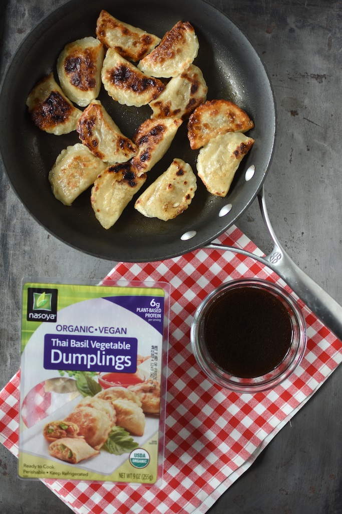 Cooked dumplings in the pan, along with dipping sauce and a package of Nasoya dumplings.