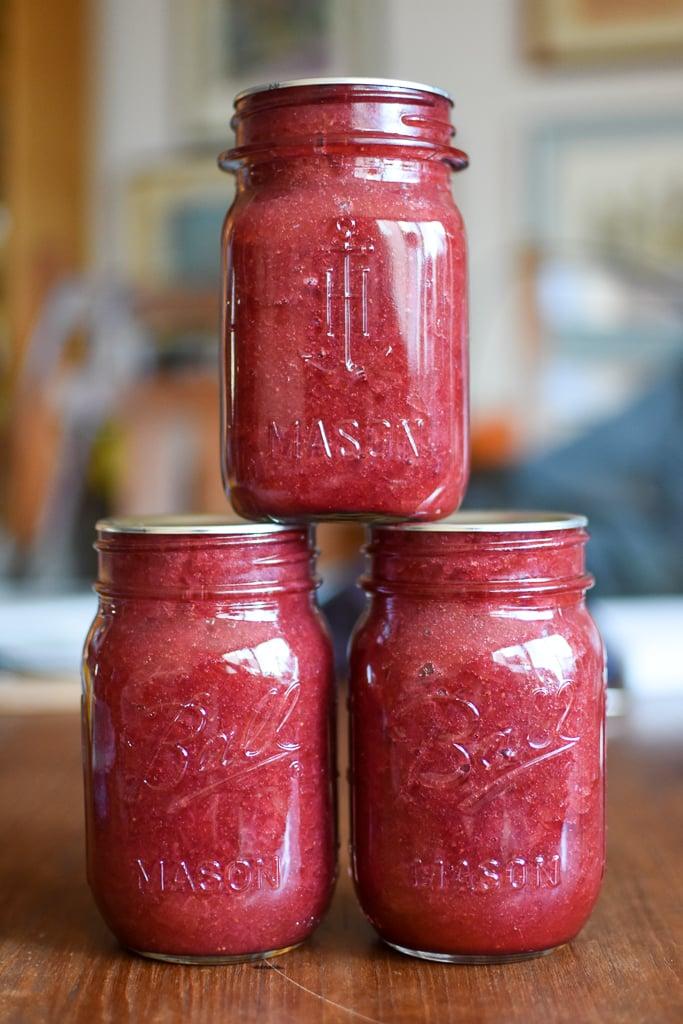 Three pint jars of low sugar strawberry rhubarb jam, stacked into small pyramid.
