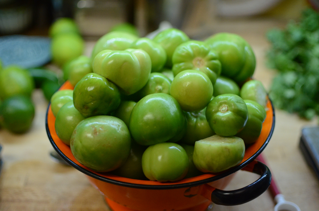An orange colander filled with four pounds of husked and washed tomatillos.