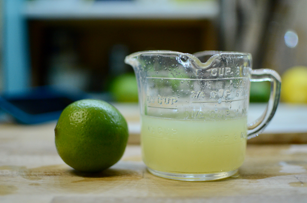 Lime and lime juice in a measuring cup.