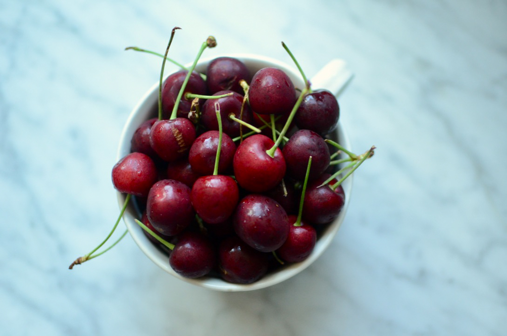 A small berry bowl filled with sweet cherries.