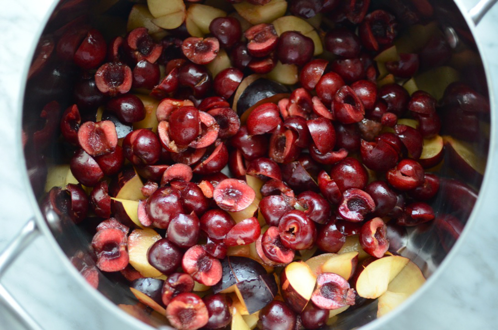 Chopped cherries and plums in a saucepan.