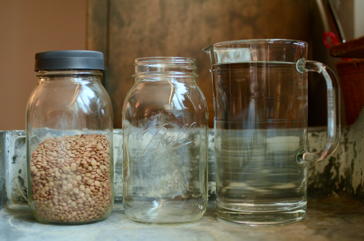 From left to right, a quart jar of brown lentils, an empty quart jar, and a pitcher of water