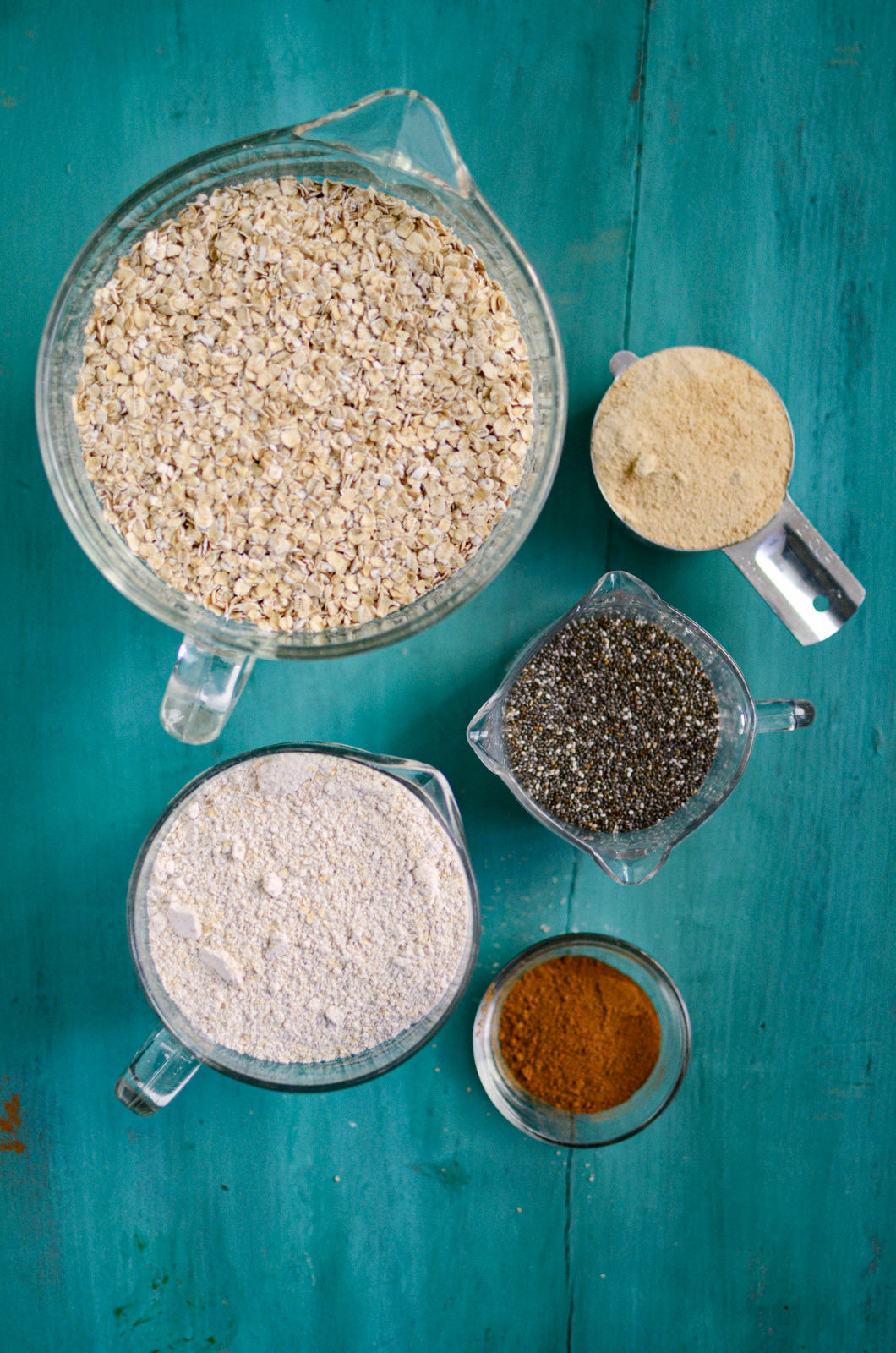 Measured ingredients for homemade instant oats in five different containers, on a blue background.