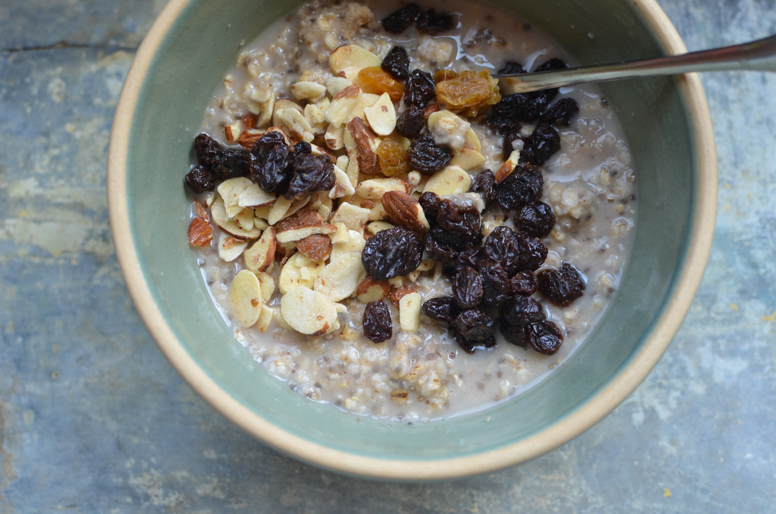 Prepared homemade instant oats in a pale green bowl, topped with raisins and sliced almonds.