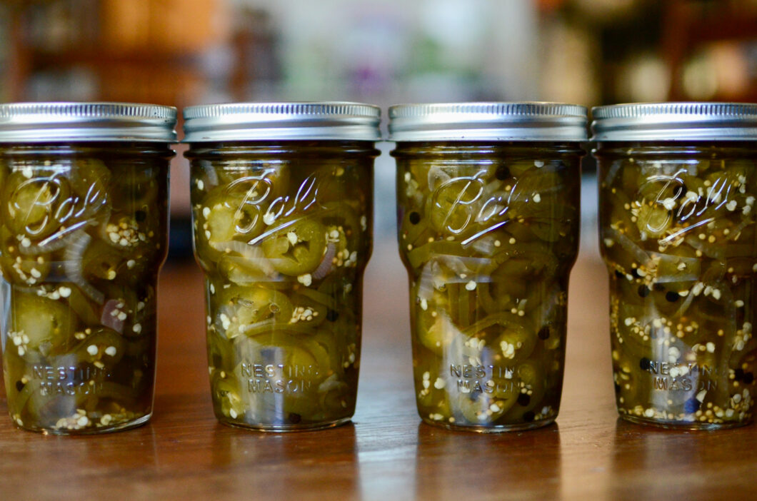 Four Ball® Nesting Pint Jars filled with dark green maple pickled jalapeños.