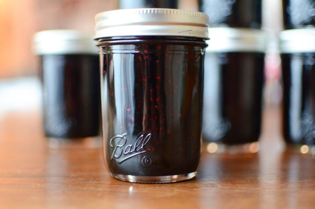 Close up of a single jar of finished black raspberry jam.