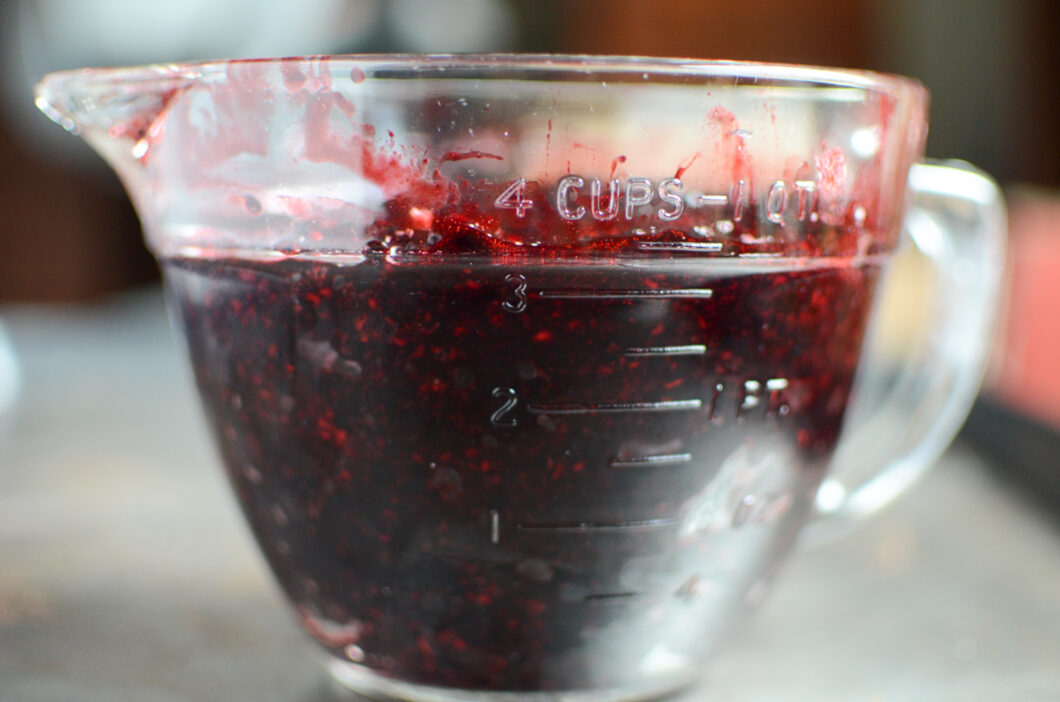 Three and a half cups of mashed black raspberries in a vintage glass measuring cup.