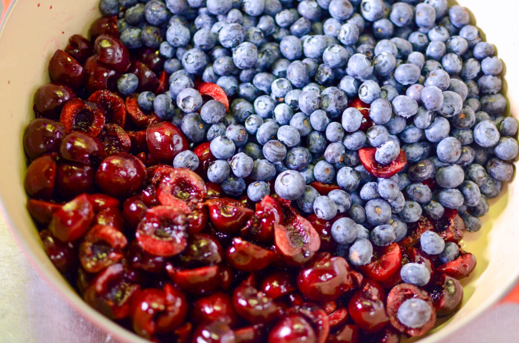 Chopped cherries and blueberries in a pot.