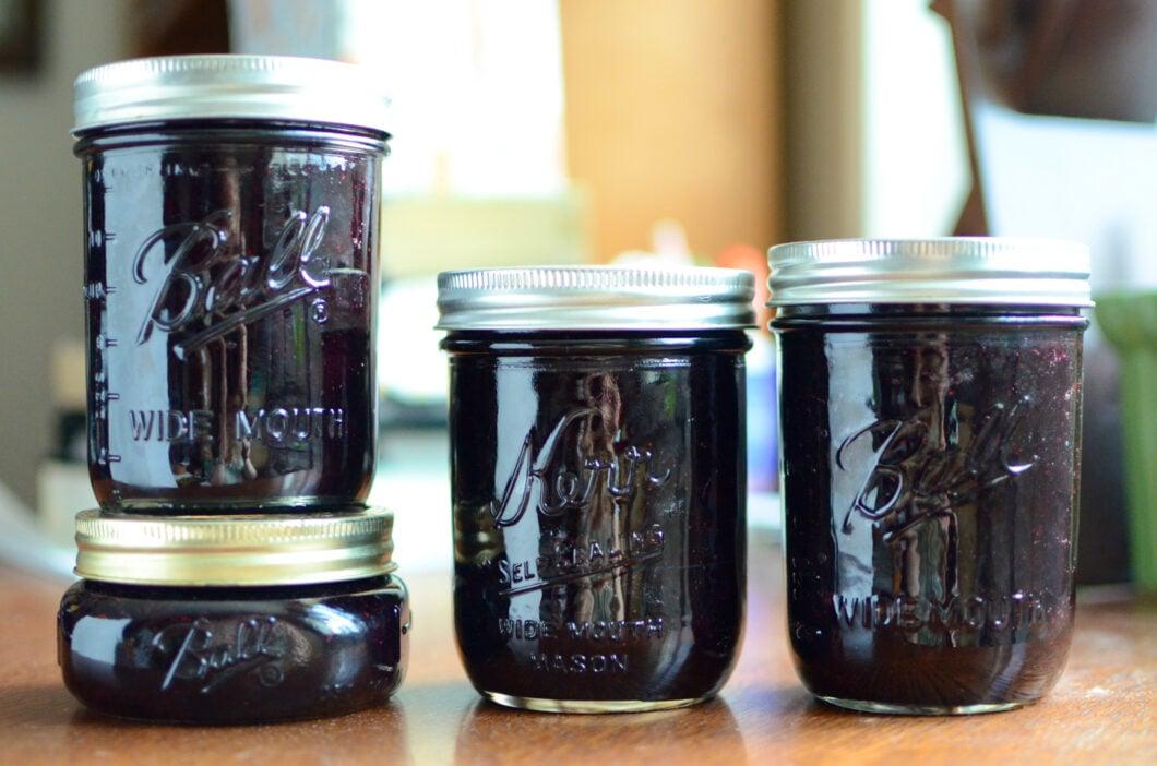 Four jars of finished cherry blueberry jam.