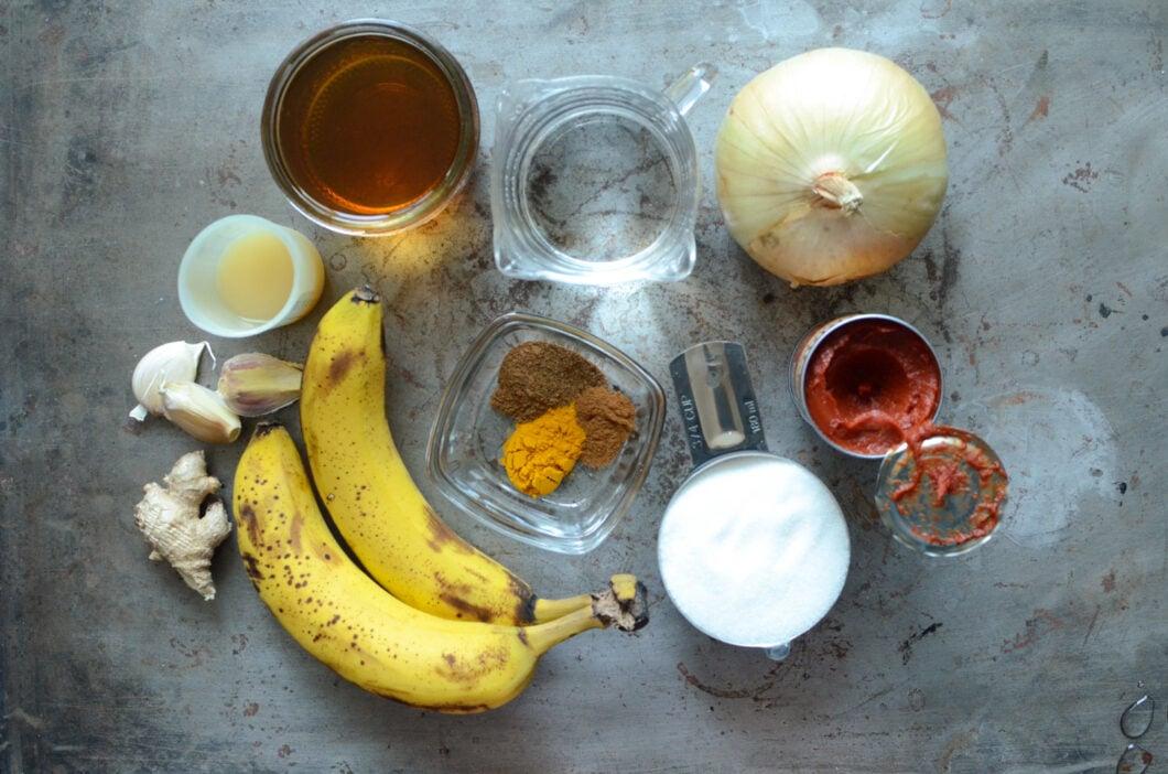 Ingredients for banana ketchup on a metal sheet pan - ginger, garlic, lemon juice, apple cider vinegar, water, onion, tomato paste, sugar, spices, and bananas.