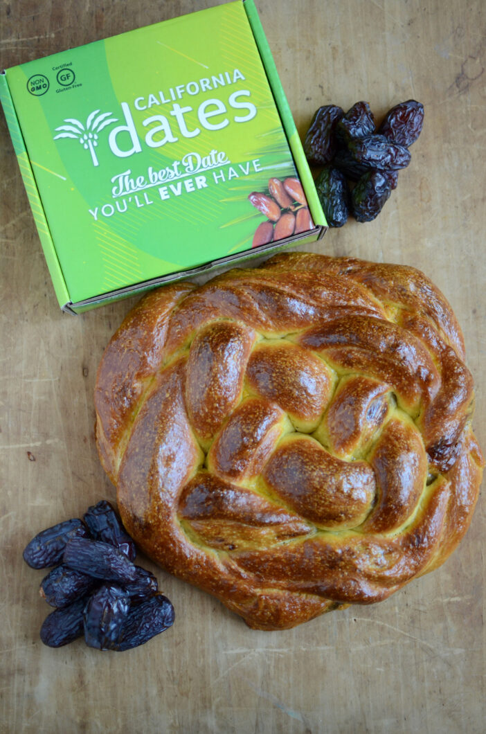 The finished loaf of filled challah, pictured with a green box of California Dates