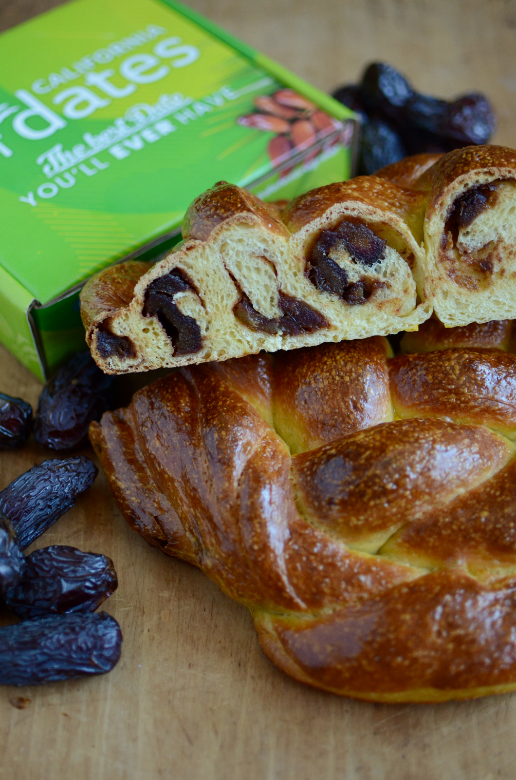 A loaf of challah, filled with apple butter and dates, sliced to show the goodness inside.