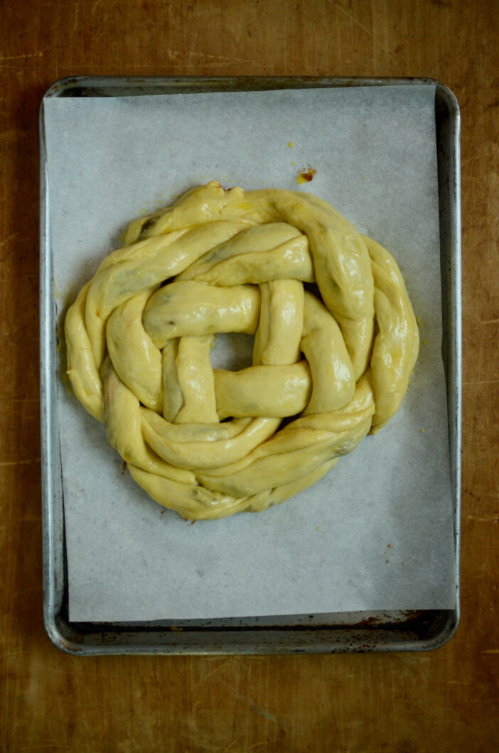 An unbaked loaf of filled challah, glazed with egg wash, before the second rise.
